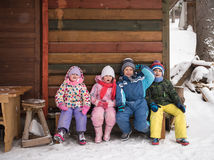 Little children group sitting  together  in front of wooden cabi Royalty Free Stock Photography