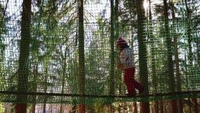 Walking through the net maze. Little children having fun on an outdoor playground in winter stock video footage