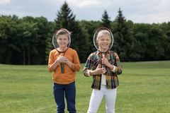 Little children holding badminton racquets and smiling at camera outdoors. Adorable little children holding badminton racquets and smiling at camera outdoors stock photos