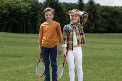 Little children holding badminton racquets and smiling at camera outdoors. Adorable little children holding badminton racquets and smiling at camera outdoors stock photo