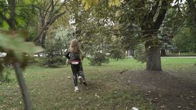 Little children holding hands and running in autumn park. Slowmotion. Two cute children are in the park. Curious boy and pretty girl hold each other hands. Kids stock video