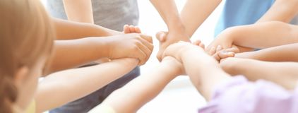 Little children holding their hands together on light background. stock photos