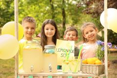 Little children at lemonade stand in park Stock Image