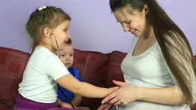 Little children listen to his brother in the stomach of pregnant mother. stock footage