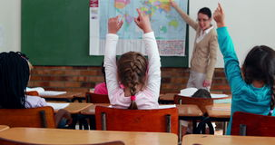 Little children listening to teacher showing the map in classroom. In elementary school stock video footage