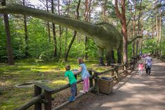 Large Diplodocus in dinosaur park. Little children looking at the massive replica of the gigantic Diplodocus dinosaur in an amusement park in Solec Kujawski Royalty Free Stock Photo