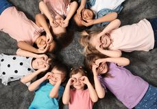 Little children lying on carpet together indoors. Kindergarten playtime activities. Little children lying on carpet together indoors, top view. Kindergarten royalty free stock photography