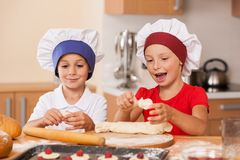 Little children making cakes and talking. Royalty Free Stock Image