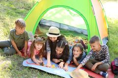 Cute children with map near tent outdoors. Summer camp. Little children with map near tent outdoors. Summer camp stock image