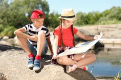 Little children with map outdoors stock image