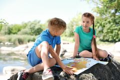 Little children with map outdoors. Summer camp stock image
