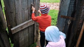 Little children open the old wooden door go for a walk on nature, slow motion