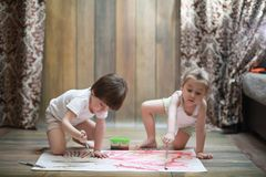 Little children paint on a large sheet of paper stock image