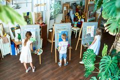 Little Children Painting in Art Studio. High angle portrait of three children painting on easels during art class in cozy studio decorated with plants, copy stock photography