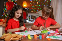 Little children painting pictures at home. Christmas celebration stock images