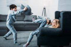 Little children in pajamas having pillow fight at home. Adorable little children in pajamas having pillow fight at home stock photo