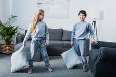 Little children in pajamas having pillow fight at home. Adorable little children in pajamas having pillow fight at home royalty free stock photo