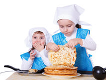 Little children with pancakes. Two cute girls playing as chefs. Surprise for Mothers Day. Isolated on a white background Royalty Free Stock Images