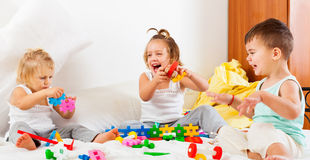Little children playing on bed stock photos