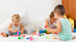 Little children playing on bed stock photo