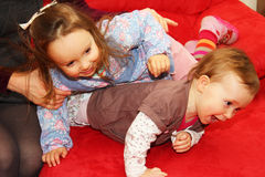 Little children playing with each other. On a red bed Royalty Free Stock Image