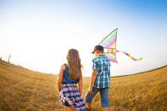 Little children playing with flying kite on the summer field Royalty Free Stock Photos