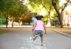 Little children playing hopscotch drawn with colorful chalk. On asphalt stock photos