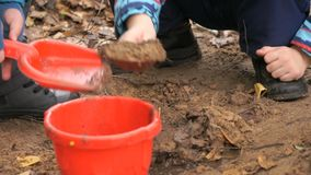 Little children playing with sand in sandbox. Children playing with sand in sandbox in an amusement park at autumn day. Close-up stock footage