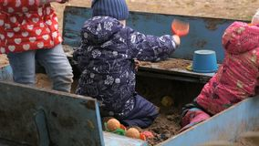 Little children playing with sand in sandbox. Outdoor in an amusement park at autumn day stock footage