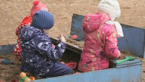 Little children playing with sand in sandbox. Outdoor in an amusement park at autumn day stock video footage