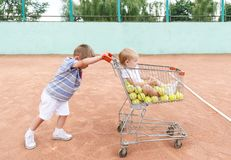 Little children playing at a tennis playground with shopping trolley stock image