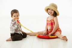 Little children playing with toy instrument. Happy kids playing on toy music instrument, little boy singing to microphone over white background Royalty Free Stock Image