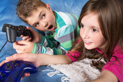 Little children playing video games Stock Images