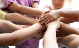 Little children putting their hands together, closeup. Unity concept stock images