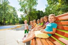 Little children rest on the bench in park Stock Photo