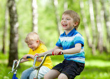 Little children riding their bikes Stock Photos