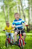 Little children riding their bikes Stock Images