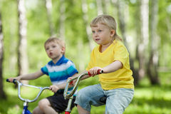 Little children riding their bikes outdoors Stock Photo
