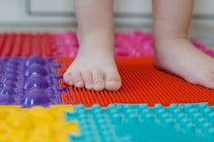 Feet on an orthopedic mattress. Little children`s feet on an orthopedic mat stock photography
