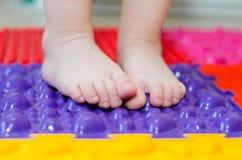Feet on an orthopedic mattress. Little children`s feet on an orthopedic mat royalty free stock photography