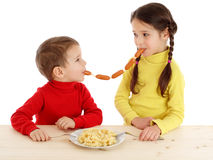 Little children sharing the chain of sausages Royalty Free Stock Photo