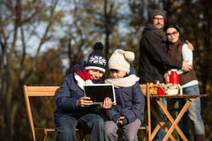 Little children sitting all together with tablet PC stock photos