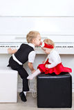 Little children sitting near piano Royalty Free Stock Photography