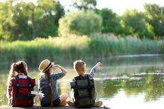 Little children sitting on wooden pier. Summer camp royalty free stock photos