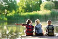 Little children sitting on wooden pier. Summer camp stock image