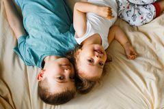 Children in soft warm pajamas playing in bed. Little children in soft warm pajamas play in bed, laugh and tumble Royalty Free Stock Photography