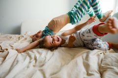 Children in soft warm pajamas playing in bed. Little children in soft warm pajamas play in bed, laugh and tumble Stock Image