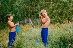 Children splash water from the sprayer outdoors royalty free stock photo