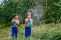 Little children splash water from the sprayer outdoors in summer stock photo