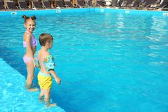 Little children standing in swimming pool. On sunny day stock image